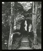 view Unidentified Garden in Germany: a walkway through a cleft in rocks in an unidentified location. digital asset: Unidentified Garden in Germany: a walkway through a cleft in rocks in an unidentified location.: [between 1910 and 1940]