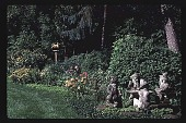 view [Brinker Hills Farm]: perennial garden, statues of elves playing cards around toadstool, and bird house and feeder. digital asset: [Brinker Hills Farm]: perennial garden, statues of elves playing cards around toadstool, and bird house and feeder.: 1997 Jul. 28.