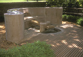 view [Cathedral Labyrinth]: Orpheus fountain bench and wooden settees in front of brick retaining wall. digital asset: [Cathedral Labyrinth]: Orpheus fountain bench and wooden settees in front of brick retaining wall.: 2004 Aug.