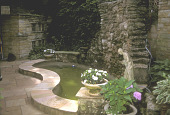 view [Secret Garden]: stone backdrop for waterfall into pond; female statue to right. digital asset: [Secret Garden]: stone backdrop for waterfall into pond; female statue to right.: 2006 Jun.