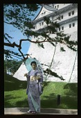 view [Nagoya Castle]: unidentified woman in traditional Japanese dress, with part of the castle in the background. digital asset: [Nagoya Castle]: unidentified woman in traditional Japanese dress, with part of the castle in the background.: 1935 May.