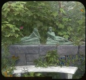 view [The Chimneys]: marble bench before a stone wall with two sculptures of figures who lounge ontop, surrounded by flowers and trees. digital asset: [The Chimneys]: marble bench before a stone wall with two sculptures of figures who lounge ontop, surrounded by flowers and trees.: [between 1914 and 1949?]
