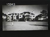 view [The Chimneys]: full view of the front of the house with woman standing in the foreground. digital asset: [The Chimneys]: full view of the front of the house with woman standing in the foreground.: [1930?]