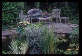 view [Ilona's Garden]: teak garden furniture placed on a bluestone patio surrounding a pool. digital asset: [Ilona's Garden]: teak garden furniture placed on a bluestone patio surrounding a pool.: 2008 May.