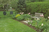 view [Apple Trees]: cottage garden with settee, chairs, and bird feeder beside tall hedge. digital asset: [Apple Trees]: cottage garden with settee, chairs, and bird feeder beside tall hedge.: 2005 May.