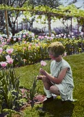 view [Onata Farm]: young girl (Miss Gertrude Watson) with bobbed hair holding a pink tulip. digital asset: [Onata Farm]: young girl (Miss Gertrude Watson) with bobbed hair holding a pink tulip.