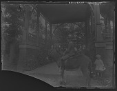 view [Tanglewood]: Walter Liebig on a donkey, with Oscar Liebig to the side under the porte-cochere. digital asset: [Tanglewood] [glass negative]: Walter Liebig on a donkey, with Oscar Liebig to the side under the porte-cochere.