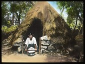 view [Miscellaneous Sites in Mexico]: a woman with a hand grinder in front of a thatched hut in an unidentified location. digital asset: [Miscellaneous Sites in Mexico]: a woman with a hand grinder in front of a thatched hut in an unidentified location.: 1937 Jan.