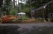 view [Obolensky Garden]: dining area on brick terrace near back of house surrounded by azaleas. digital asset: [Obolensky Garden]: dining area on brick terrace near back of house surrounded by azaleas.: 2003 May.