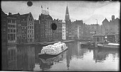 view [Miscellaneous Sites in the Netherlands]: looking across the Damrak in Amsterdam, with the tower of the Oude Kerk (Old Church) in the distance. digital asset: [Miscellaneous Sites in the Netherlands] [negative]: looking across the Damrak in Amsterdam, with the tower of the Oude Kerk (Old Church) in the distance.