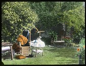 view [Truslow Garden]: chairs and table set up for tea in the garden. digital asset: [Truslow Garden] [lantern slide]: chairs and table set up for tea in the garden.