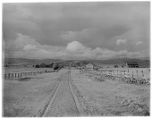 view [Miscellaneous Sites in the Adirondack Mountains]: an unidentified location with a dirt road and farm buildings. digital asset: [Miscellaneous Sites in the Adirondack Mountains] [glass negative]: an unidentified location with a dirt road and farm buildings.