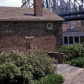 view [Mount Vernon Hotel Museum and Gardens]: museum building, with lilacs in foreground and Queensboro (59th Street) Bridge looming overhead. digital asset: [Mount Vernon Hotel Museum and Gardens] [slide]: museum building, with lilacs in foreground and Queensboro (59th Street) Bridge looming overhead.
