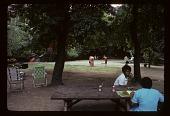 view Cooper-Hewitt Museum: ladies sitting at park bench, drinking Tab soda; children playing in the background. digital asset: Cooper-Hewitt Museum: ladies sitting at park bench, drinking Tab soda; children playing in the background.: 1974 Jul.