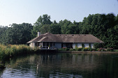 view [Valley View Farm]: view across the pond of the north side of the house, perennial garden, and decking. digital asset: [Valley View Farm]: view across the pond of the north side of the house, perennial garden, and decking.: 2007 Jun.