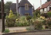 view [Dishman Garden]: front perennial garden and wrought iron fence with sidewalk in foreground. digital asset: [Dishman Garden]: front perennial garden and wrought iron fence with sidewalk in foreground.: 2005 Jul.