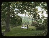 view [Breeze Hill]: Couple; girls; under tree in garden. digital asset: [Breeze Hill] [lantern slide]: Couple; girls; under tree in garden.