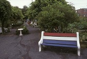 view [Aspen Farms Community Garden]: red, white and blue painted benches on paved walkways with birdbath in center. digital asset: [Aspen Farms Community Garden]: red, white and blue painted benches on paved walkways with birdbath in center.: 2004 Sep.