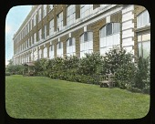 view [Hershey Department Store]: lawn and bushes outside the store and the large stone house owned by Edwin Hershey. digital asset: [Hershey Department Store] [slide]: lawn and bushes outside the store and the large stone house owned by Edwin Hershey.