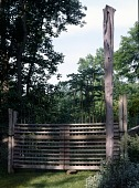 view [Tohickon Hill]: the custom-made gate and column are back by rail fences lined with wire to protect the garden. digital asset: [Tohickon Hill] [transparency]: the custom-made gate and column are back by rail fences lined with wire to protect the garden.