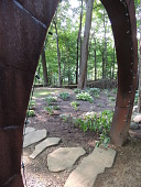 """view [Moments]: a view of the hosta garden, the curly willow fence, the suspension bridge, and stone walkway is seen through the """"Moon Gate"""" arch. digital asset: [Moments]: a view of the hosta garden, the curly willow fence, the suspension bridge, and stone walkway is seen through the """"Moon Gate"""" arch.: 2016 Sep."""