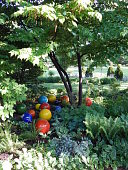view [Wolf Bend Garden]: ceramic balls block the path to deter deer. The boxwood balls in the distant bed were inspired by a Japanese garden. digital asset: [Wolf Bend Garden]: ceramic balls block the path to deter deer. The boxwood balls in the distant bed were inspired by a Japanese garden.