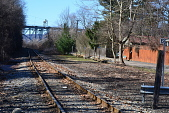 view [Choderwood]: Outside the privacy fence there are disused railroad tracks and a view of an automobile bridge. digital asset: [Choderwood]: Outside the privacy fence there are disused railroad tracks and a view of an automobile bridge.