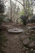 view [GATOP]: millstone set in woodland path; bronze sculpture at top. digital asset: [GATOP]: millstone set in woodland path; bronze sculpture at top.: 2006.