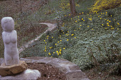 """view [GATOP]: stone path forks past marble statue """"Lot's Wife"""" with view of woodland garden of spring-flowering pachysandra, forsythia and daffodils. digital asset: [GATOP]: stone path forks past marble statue """"Lot's Wife"""" with view of woodland garden of spring-flowering pachysandra, forsythia and daffodils.: 2006."""