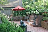 view [Wellford Garden]: the brick terrace wall is lined with potted plants, two griffin urns flank the brick stairs. digital asset: [Wellford Garden]: the brick terrace wall is lined with potted plants, two griffin urns flank the brick stairs.: 2010 May.