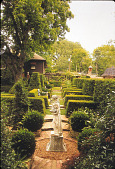 view [Holly Cottage Garden]: terraced, grass narrow walkway with brick steps between geometric topiaries. digital asset: [Holly Cottage Garden]: terraced, grass narrow walkway with brick steps between geometric topiaries.: 2005 May.