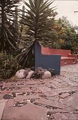 view [Jardin De Mil Flores]: curved pink and blue concrete bench at brick, stone, and pebble walkway; Spanish Bayonet to left. digital asset: [Jardin De Mil Flores]: curved pink and blue concrete bench at brick, stone, and pebble walkway; Spanish Bayonet to left.: 2005 Oct.