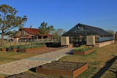 view [Crenshaw Farm]: kitchen-barn next to greenhouse with raised flower beds and brick walkway. digital asset: [Crenshaw Farm]: kitchen-barn next to greenhouse with raised flower beds and brick walkway.: 2016 Feb.