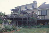 view [A Country Garden]: view of deck featuring containers, pergola, plant supports, and bird feeders. digital asset: [A Country Garden]: view of deck featuring containers, pergola, plant supports, and bird feeders.: 2002 Jul.
