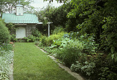view [Poke Garden]: grass walkway between perennial beds leads to green-roofed tool shed with cupola. digital asset: [Poke Garden]: grass walkway between perennial beds leads to green-roofed tool shed with cupola.: 2005 Jun.