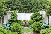 view [Tregaron]: two parterres inside the stucco walls that surround the cottage garden, with crab apple trees, hosta and boxwood. digital asset: [Tregaron]: two parterres inside the stucco walls that surround the cottage garden, with crab apple trees, hosta and boxwood.: 2014 Jun.