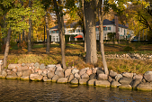 view [House in the woods]: rockwork along the lakeshore and the nearby walkway with the main house in the distance. digital asset: [House in the woods]: rockwork along the lakeshore and the nearby walkway with the main house in the distance.: 2011 Oct.