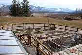 view [Riverview Ranch]: Fall garden put to bed with remnants of fall leaves and snow creeping down the hills; the wagon wheel designed flower garden and raised garden beds are visible. digital asset: Fall garden put to bed with remnants of fall leaves and snow creeping down the hills; the wagon wheel designed flower garden and raised garden beds are visible.