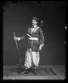 view Fares A. Ferzan Models Syrian Costume with Sword, Dagger, and Rifle (front) digital asset number 1
