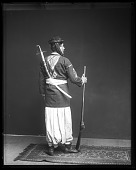 view Fares A. Ferzan Models Syrian Costume with Sword, Dagger, and Rifle (back) digital asset number 1