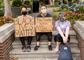 """view Women holding """"Black Lives Matter"""" and """"This Teacher believes Black Lives Matter"""" signs digital asset: Three women holding signs sitting on steps"""