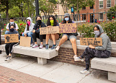 view Protesters holding signs while sitting on benches digital asset: Group of young women holding signs sitting on benches
