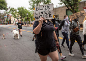"view Protester with ""Black Lives Matter"" sign digital asset: Woman marching with ""Black Lives Matter"" sign"