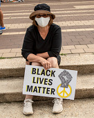 """view Woman sitting on steps holding """"Black Lives Matter"""" sign digital asset: Woman sitting on steps holding """"Black Lives Matter"""" sign"""