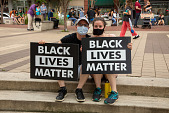 """view young man and woman sitting on steps holding """"Black Lives Matter"""" signs digital asset: young man and woman sitting on steps holding """"Black Lives Matter"""" signs"""