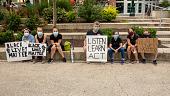 """view Adults and children sitting and holding """"Black Lives Matter"""" signs digital asset: Adults and children sitting and holding """"Black Lives Matter"""" signs"""