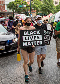 """view Woman and man holding """"Black Lives Matter"""" signs digital asset: Woman and man holding """"Black Lives Matter"""" signs"""