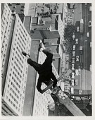 view [Man dunking donuts while standing on his head on top of a sky scraper]: [black-and-white photoprint] digital asset: [Man dunking donuts while standing on his head on top of a sky scraper]: [black-and-white photoprint]