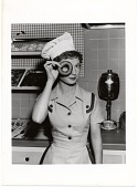 view [Pert young waitress in restaurant peeking through a donut hole : black-and-white photoprint.] digital asset: [Pert young waitress in restaurant peeking through a donut hole : black-and-white photoprint.]