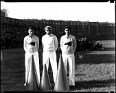 view Howard University cheerleaders Hallie Taylor, Tommie Andrews, and Hobson standing on a sports field each with a megaphone placed in front of them. digital asset: untitled